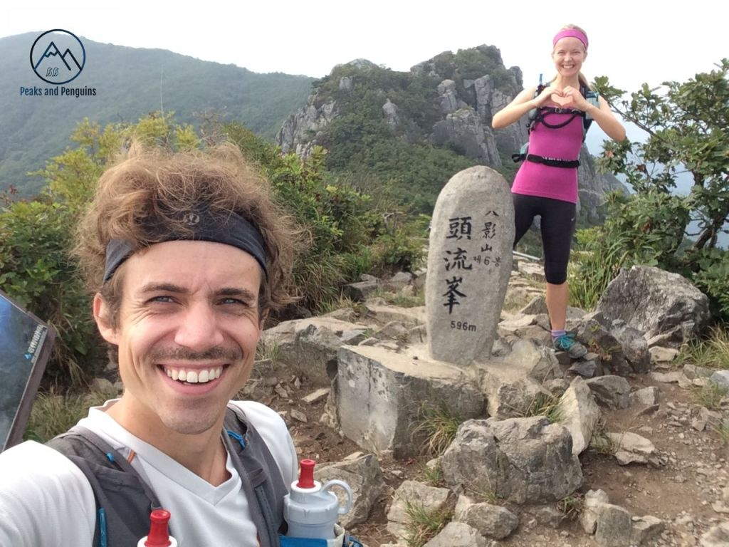 An image of the author, Carrie, and her husband, Kent, standing on a mountain peak in Dadohaehaesang National Park. Kent is in the foreground, taking a selfie. Carrie is in the background, standing just behind the summit stele, with her hands formed into the shape of a heart in front of her chest.