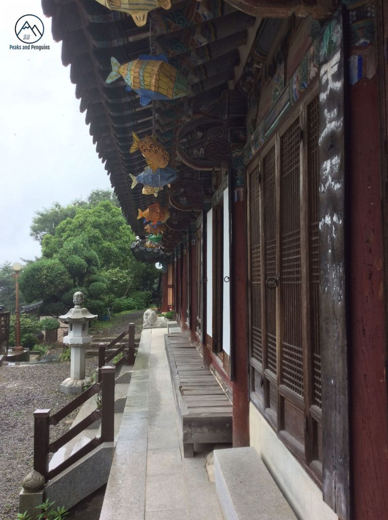An image of a temple. The image was taken from the corner of one temple building, so the view is along the outer front wall. A series of latticework wooden doors are alternately open and closed. There are colorful paper lanterns in the shapes of fish hanging from the traditional overhanging roof.