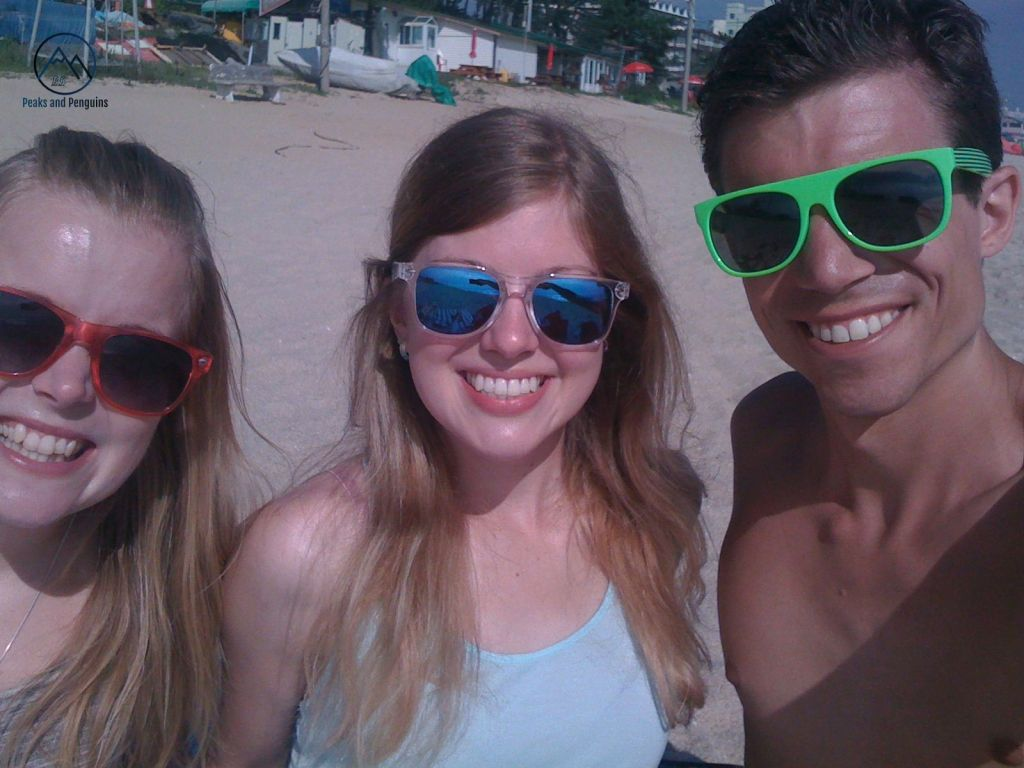 An image of a trio of happy beach goers! The author is on the left, in pink sunglasses, with her sister in blue mirrored sunglasses in the middle. Her husband is on the right, wearing green sunglasses. The three are sitting on a sandy beach.