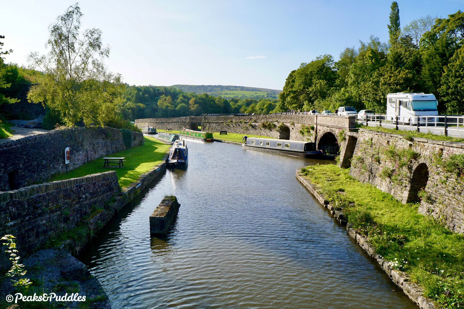 Brookside crosses Bugsworth Basin on the final bridge of the Peak Forest Canal, number 61 (Chinley Road Bridge).