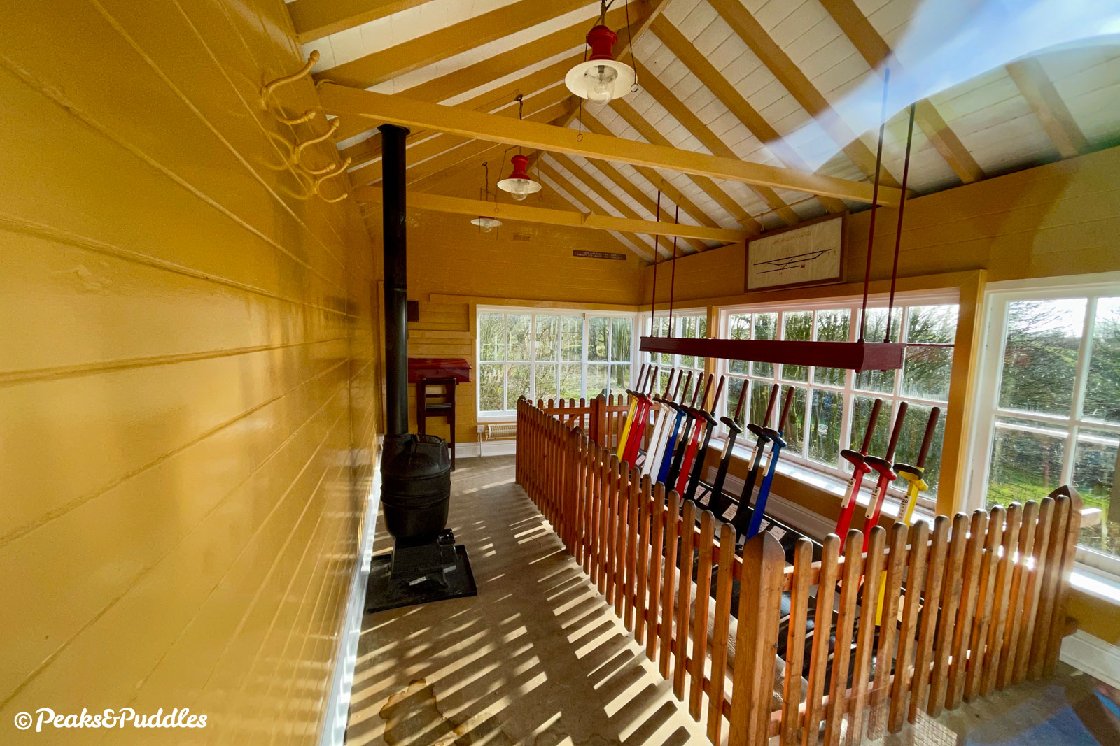 Inside Harrington Signal Box, with its colourful levers, stove, desk and track layout plan.