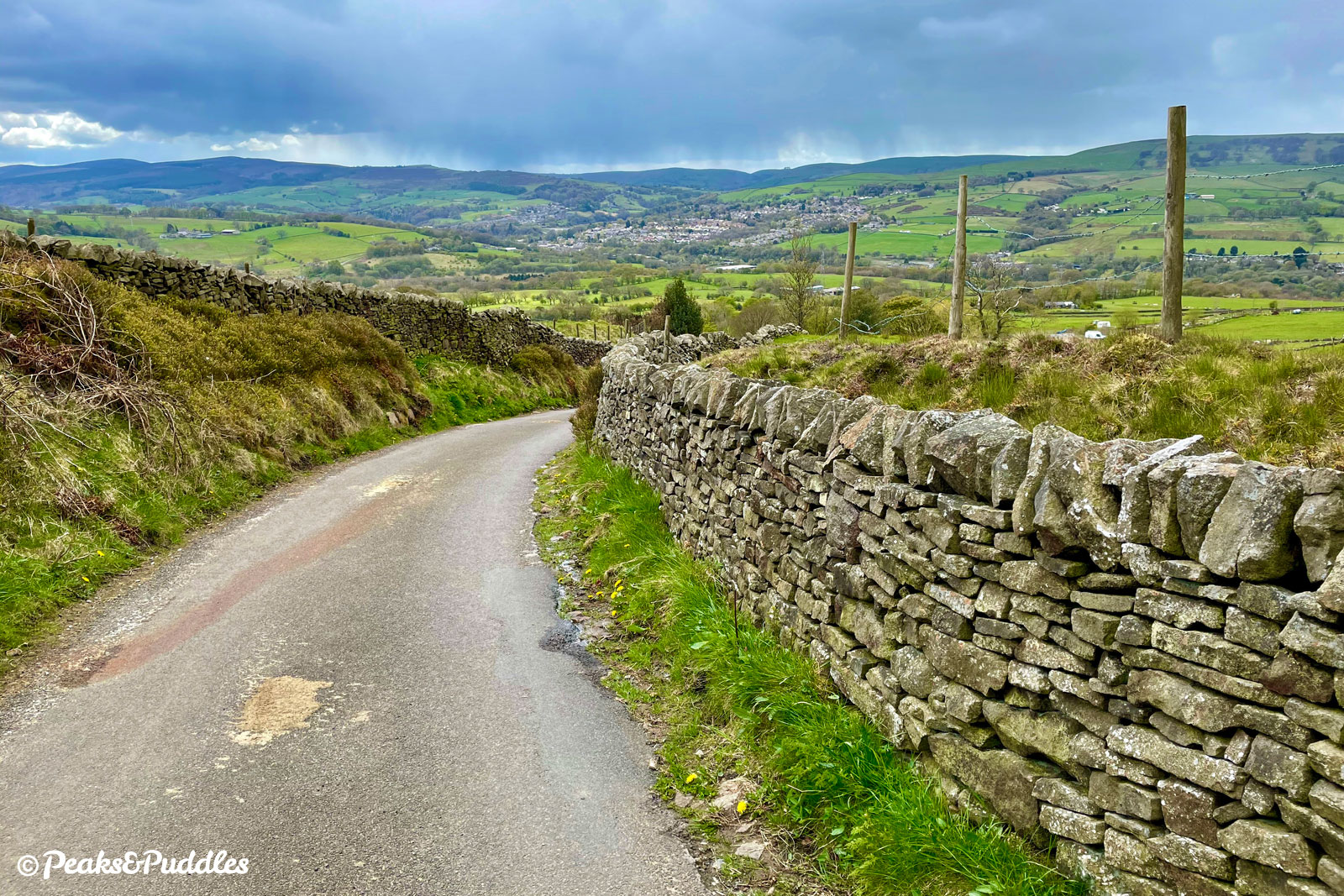 With Whaley Bridge central in the distance and the Tors of the Upper Goyt Valley to the left, the lane falls down the side of Chinley Churn.
