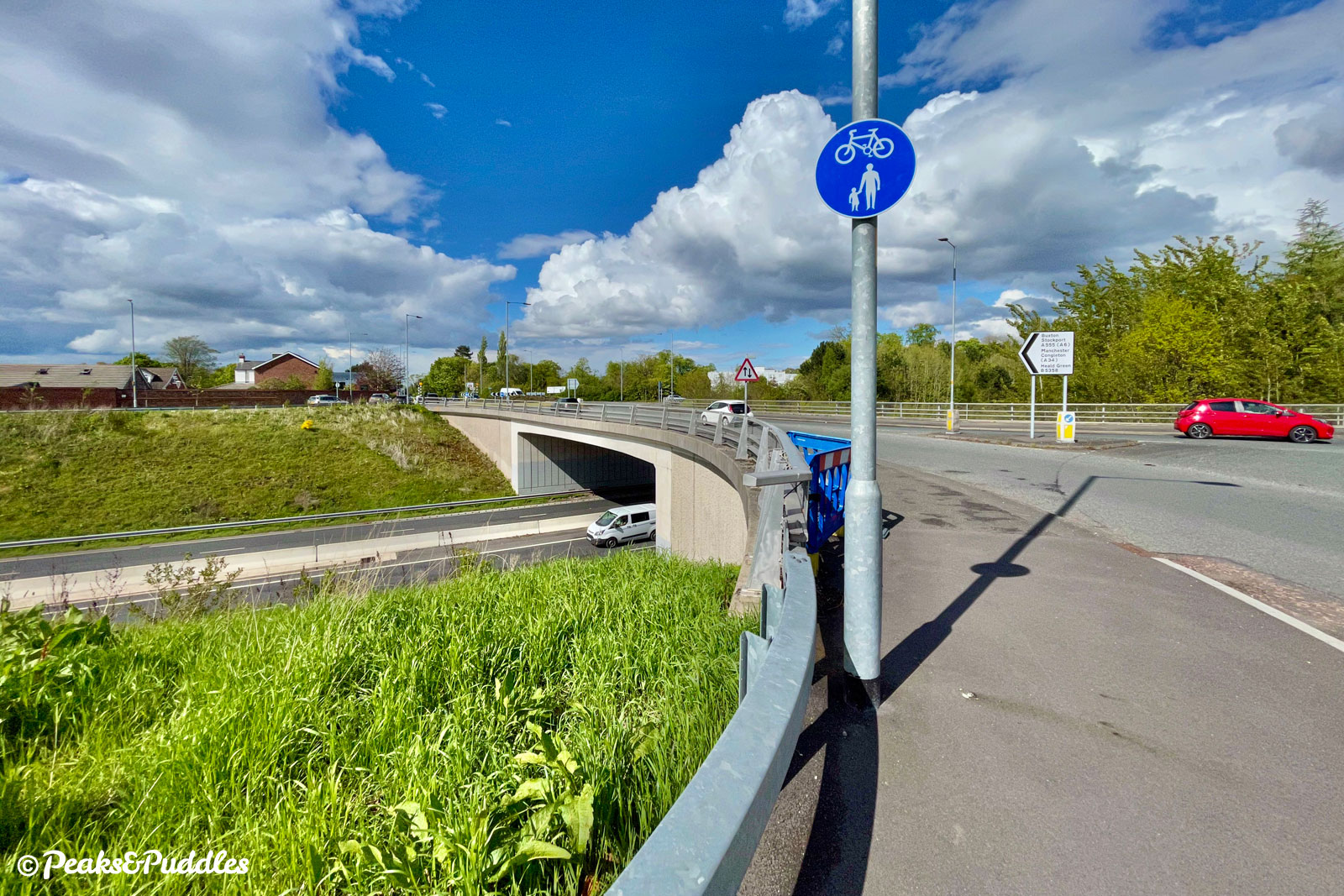 Join the shared pavement to the left via the dropped kerb before the roundabout and follow it over the bridge.