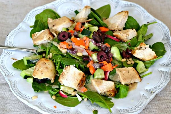 Whole30 compliant chicken salad over spinach and arugula with pine nuts, radishes, carrots, cucumbers and kalamata olives.