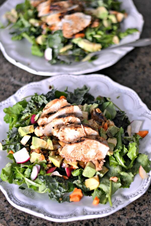 Whole30 compliant seared chicken salad over kale and arugula with radishes, carrots, avocado, spiced walnuts and apples.