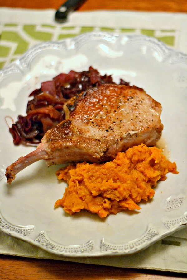 Whole30 approved dinner of bone-in pork chops with mashed sweet potatoes and braised red cabbage and apples.