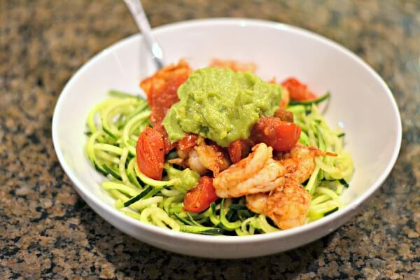 Whole30 compliant fajita-seasoned shrimp and tomatoes over zoodles with guacamole.