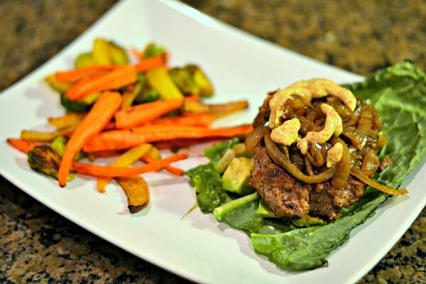 Whole30 approved burger in a kale wrap with avocado and caramelized onions and roasted carrots, brussels and turnips.