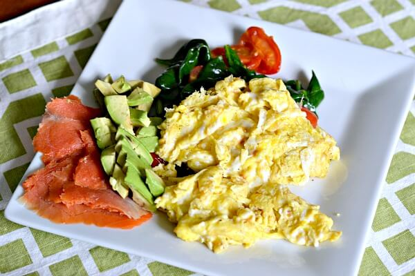 Whole30 compliant meal of scrambled eggs, sauteed spinach and tomatoes, avocado and smoked salmon.