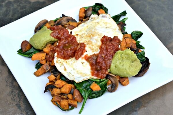 Whole30 approved sweet potato, mushrooms, spinach and fried egg with salsa and guacamole.