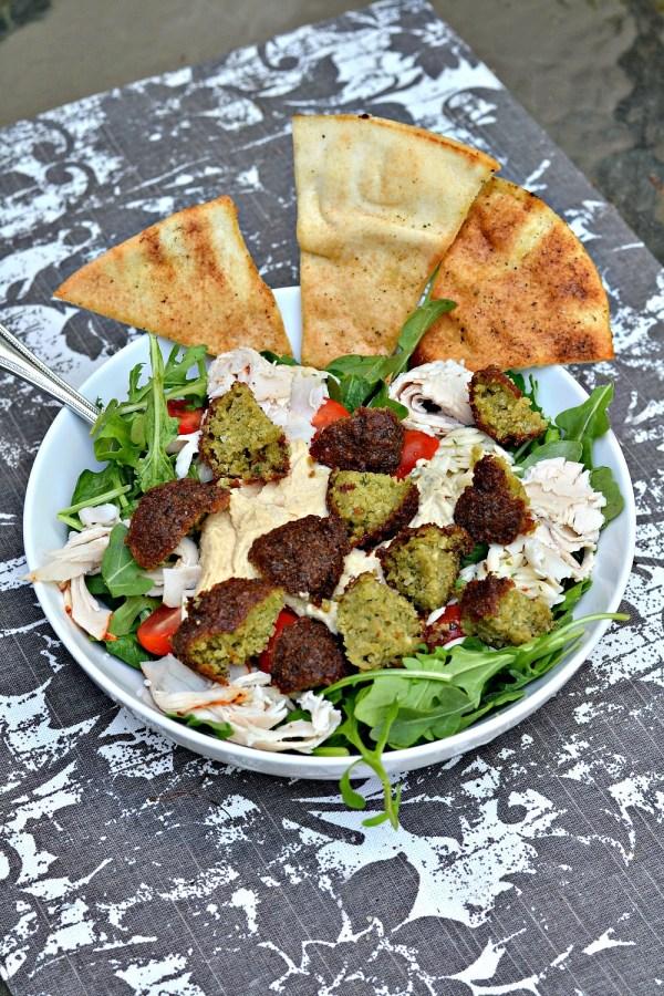 Salad with spinach, arugula, tomatoes, deli turkey, falafel, lemon pine nut orzo, hummus, baba ganoush and homemade pita chips