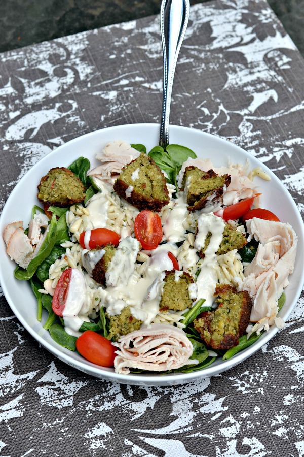 Salad with spinach, lemon pine nut orzo, tomatoes, falafel, deli turkey and tahini dressing