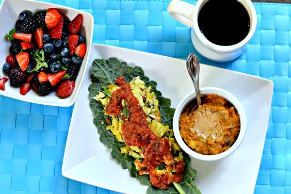 Scrambled egg tacos in lacinto kale leaves with mashed sweet potatoes and berries