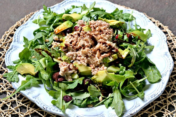 Salad with arugula, spinach, kalamata olives, pine nuts, avocado, dried cranberries and canned salmon