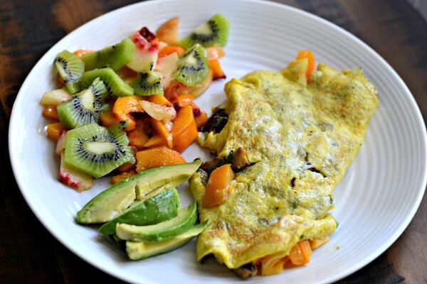 two egg omelet with mushrooms, zucchini and heirloom tomatoes, sliced avocado and fresh fruit