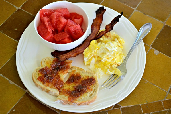 Two slices of uncured applewood smoked bacon, two scrambled eggs, a slice of sourdough toast with butter and jam and watermelon