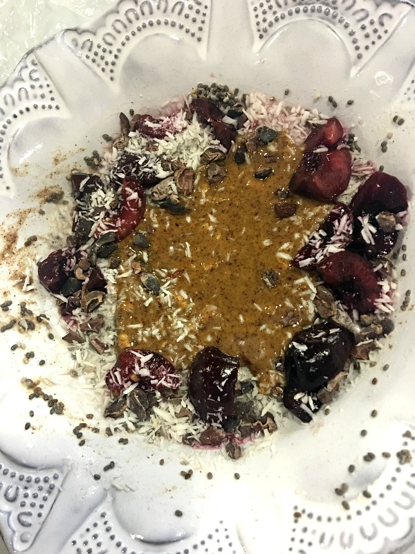Chia pudding topped with frozen cherries, almond butter, unsweetened coconut and cacao nibs.