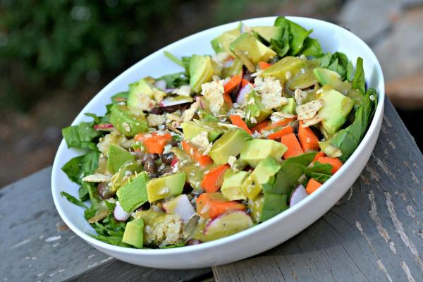 chopped spinach with quinoa, avocado, black beans, carrots, radishes and crushed tortilla chips with avocado vinaigrette