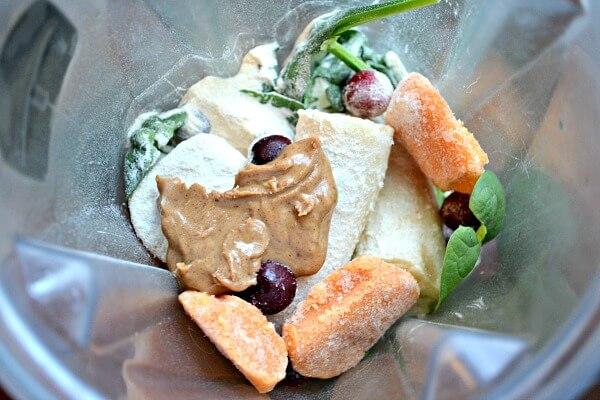 holiday-themed smoothie with frozen banana, frozen sweet potatoes, frozen fresh cranberries, spinach, Silk Almond Nog, almond butter and Premier Protein Vanilla Milkshake Whey