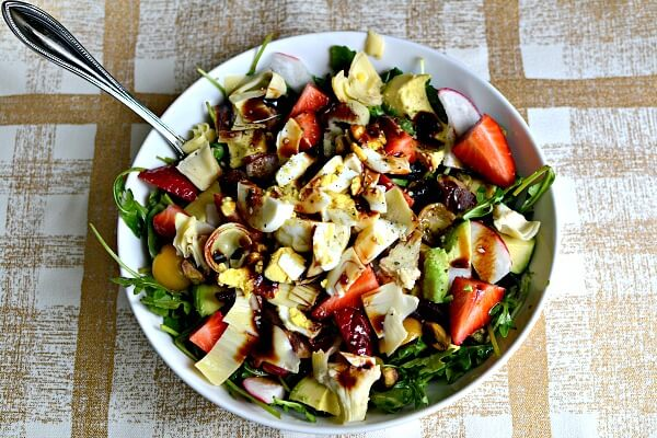Arugula, artichokes, tomatoes, strawberries, avocado, radishes, dried apricots, hardboiled egg, olive oil, lemon juice, balsamic and sea salt.