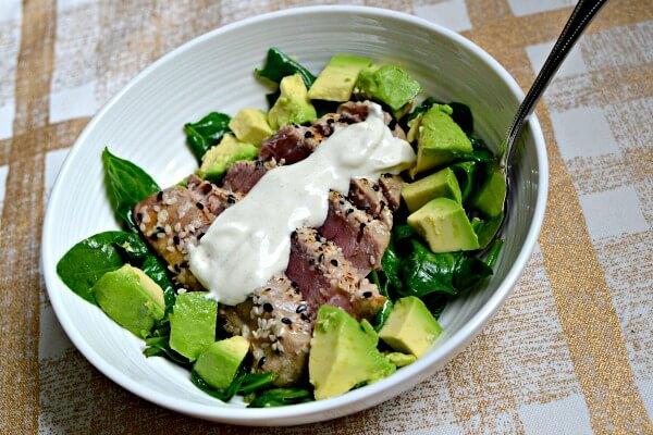 Sesame seared tuna over sauteed spinach with avocado and wasabi aioli.