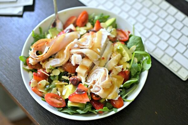 Salad with spinach, arugula, tomatoes, sliced almonds, dried cranberries, avocado, strawberries and deli turkey with a sesame ginger dressing