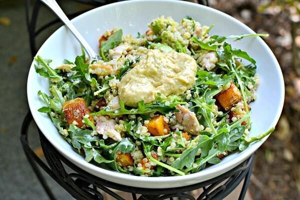 Arugula, quinoa and leftover shredded chicken thighs and butternut squash tossed with Tessamae's Zesty Ranch. Hummus on top.