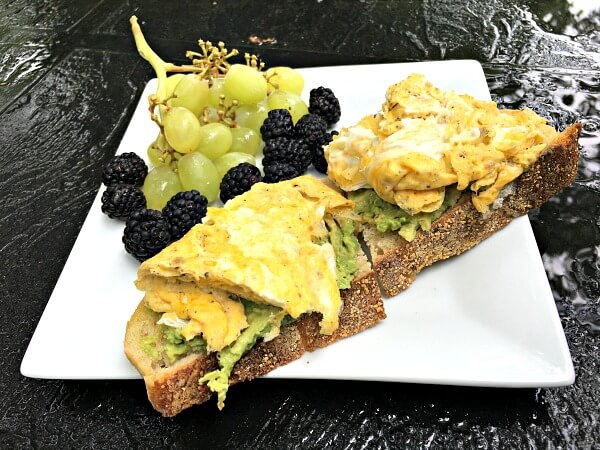 Scrambled eggs over avocado toast with fruit