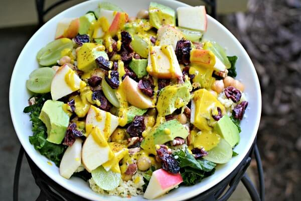 Kale, grapes, apples, toasted pecans, dried mixed berries, avocado, leftover couscous and tahini turmeric dressing.