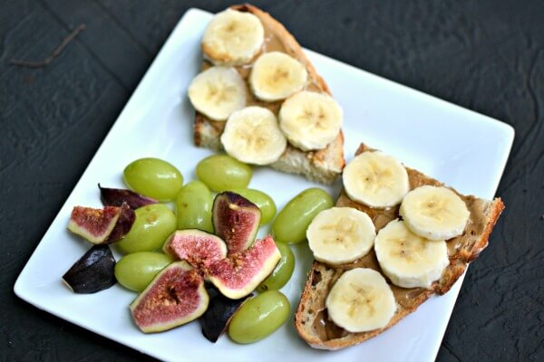 Sourdough toast with sunflower seed spread, honey and bananas and fruit on the side.