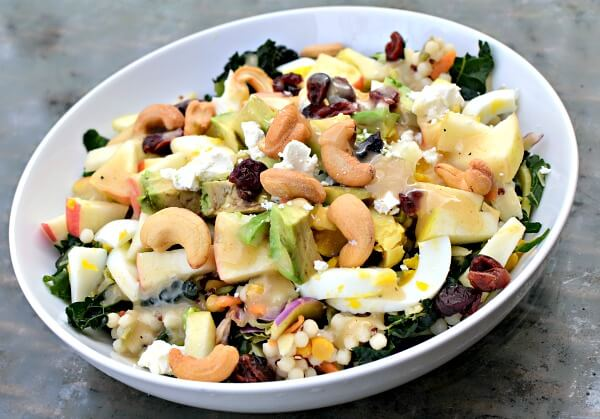 Massaged greens, cous cous, hardboiled egg, avocado, cashews, dried cranberries, apples, feta