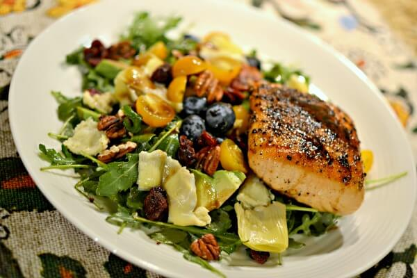 arugula salad with blueberries, artichoke hearts, yellow cherry tomatoes, dried cranberries, avocado and pecans with a side of pan seared salmon