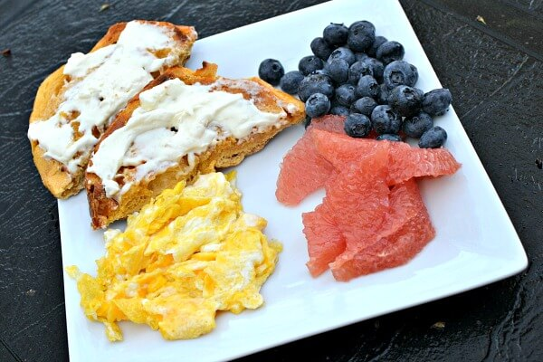 bagel with cream cheese, eggs and fruit