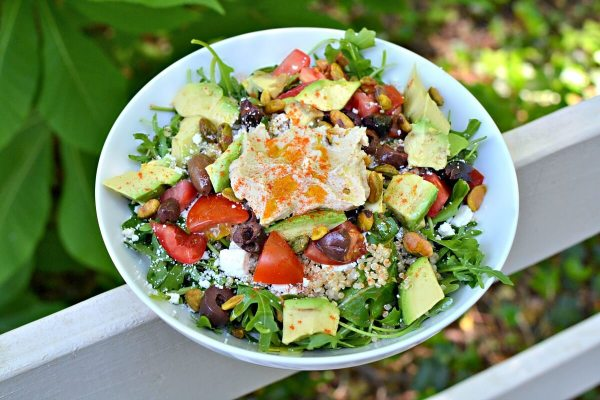 salad with arugula, quinoa, hummus, avocado, tomatoes, feta and olives