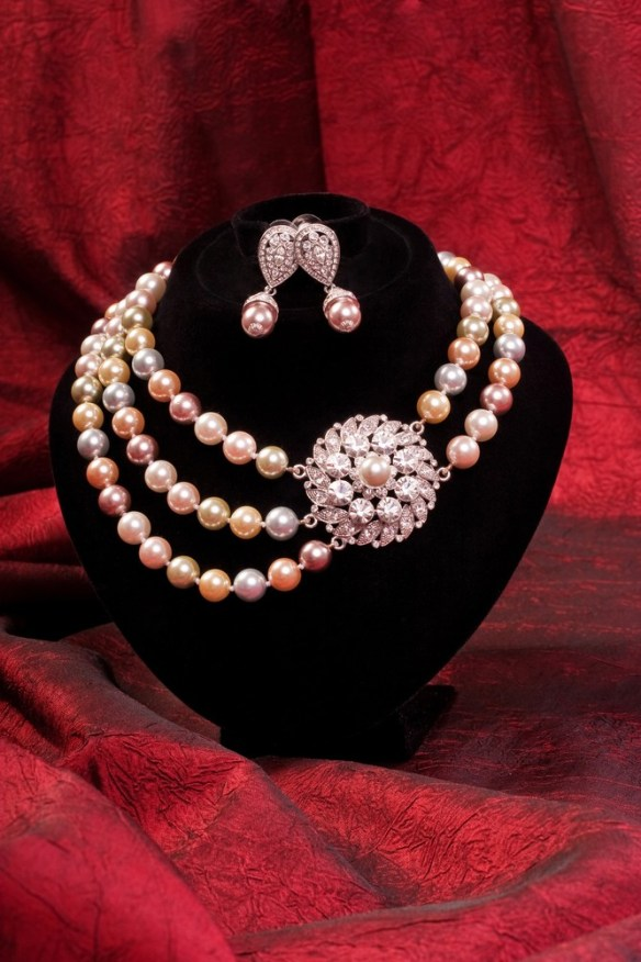 Pearl choker and earring on a red background