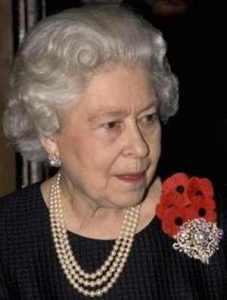 queen elizabeth II wearing a triple strand pearl necklace