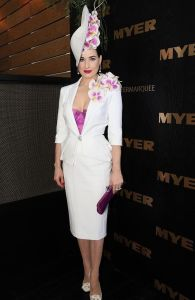 dita von teese wearing a white suit with white pearl earrings