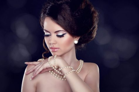 woman wearing layers of pearl necklaces