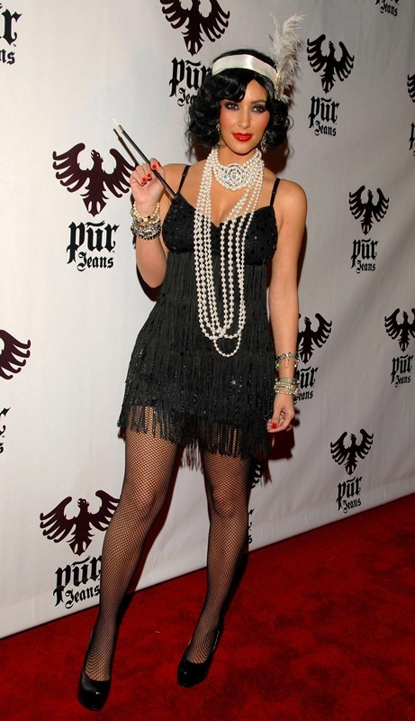 """a2c35b5c15288 ... fringed flapper-style black dress with fishnet tights, layered  bracelets, classic black """"cigarette holder"""", an ivory peacock feather  headpiece, ..."""