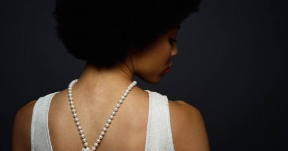 young woman with pearl necklace on her back photo