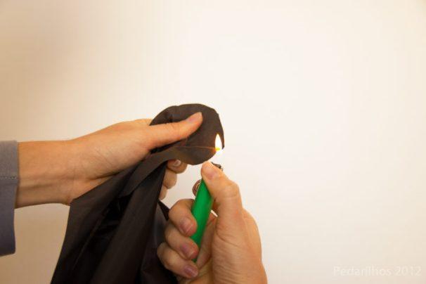 Com Isqueiro ou vela, aproxime a chama das bordas para derreter suavemente as beiradas e evitar que o tecido desfie