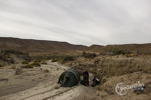 Acampamento selvagem protegidos dos ventos insanos da Ruta-40 no barranco formado pela água, no leito de um rio agora seco.
