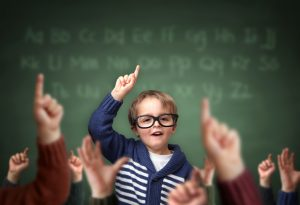 Elementary student school child with hand raised in the classroom in front of a blackboard with other children concept for teacher's pet, standing out from the crowdand, genius or excelling in education