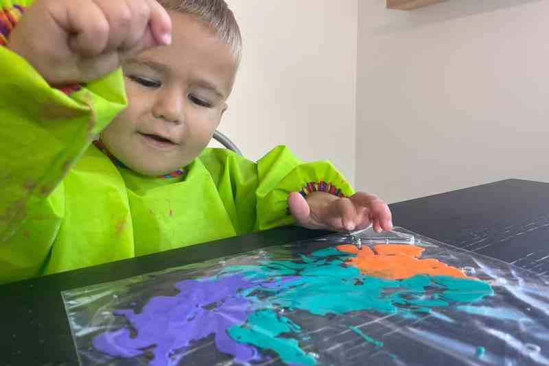 Toddler having fun painting with paint in a zip top bag
