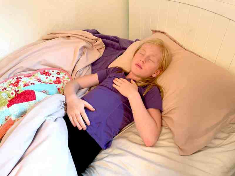 Child laying in bed in yoga pose using mindfulness technique to fall asleep.