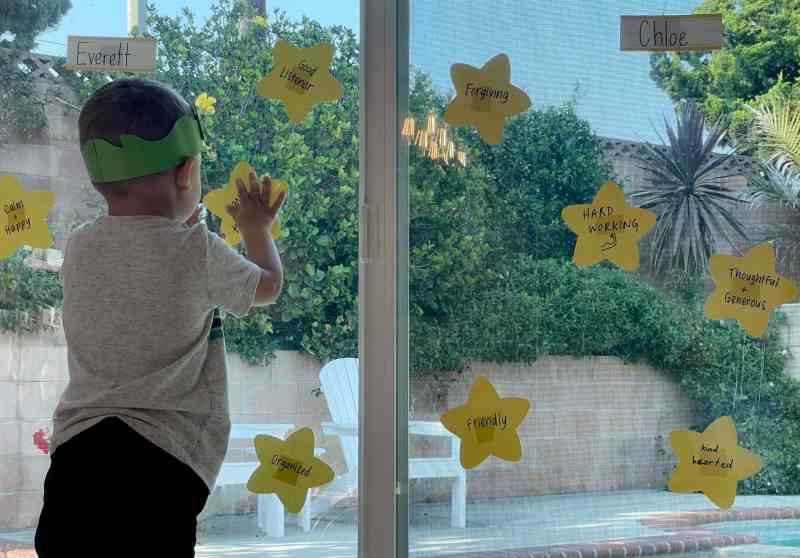 Child sticking starts with positive messages on a window.