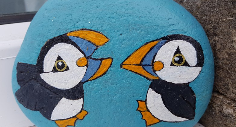 A pebble painted with 2 puffins by one of our recent guests