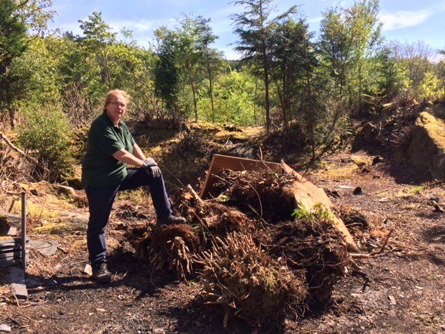 Carrie in casual pose over the current bonfire heap of rhodo stumps