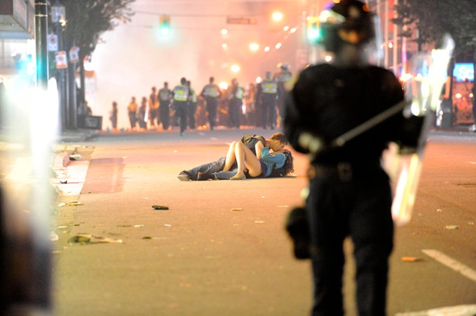 Riot police walk in the street as a couple kisses on June 15, 2011 in Vancouver, Canada. Vancouver broke out in riots after their hockey team the Vancouver Canucks lost in Game Seven of the Stanley Cup Finals.