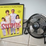 "a small fan next to a dvd copy of ""the Stupids"""